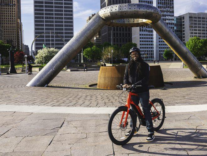 Jason Hall standing with Super Commuter+ beside Detroit fountain.