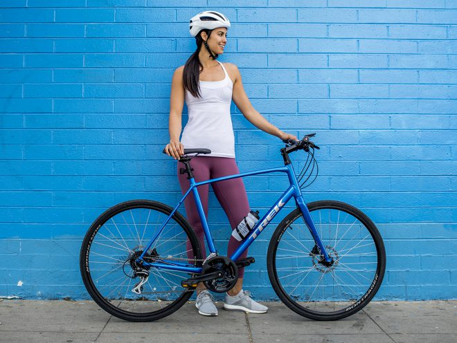 Fitness model standing beside brick wall and holding new Trek FX bike.