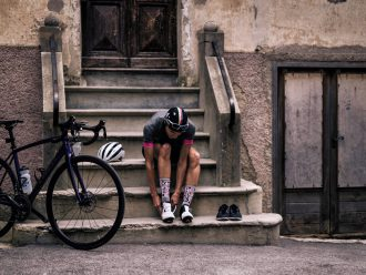 Cyclist putting on shoes while sitting on steps