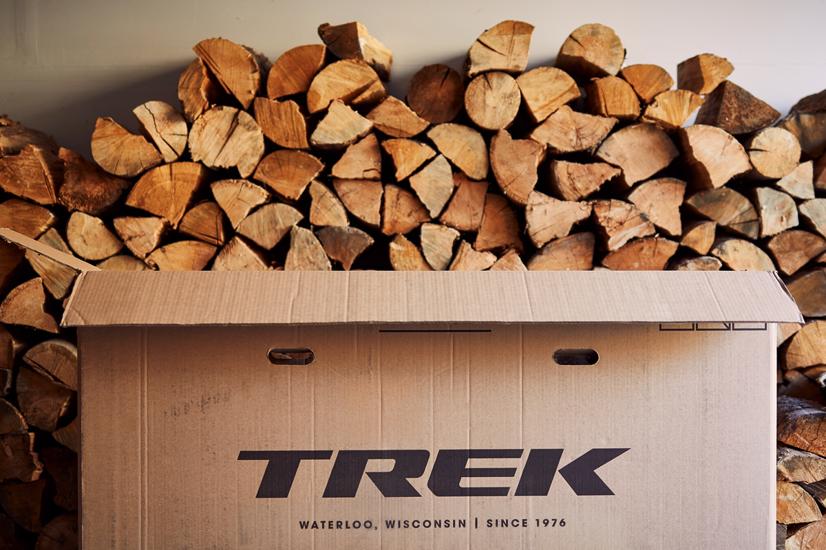 A cardboard Trek bike box in front of a stack of chopped wood.