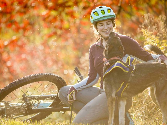 Blair Braverman enjoys a moment with one of her dogs amid beautiful autumn foliage.