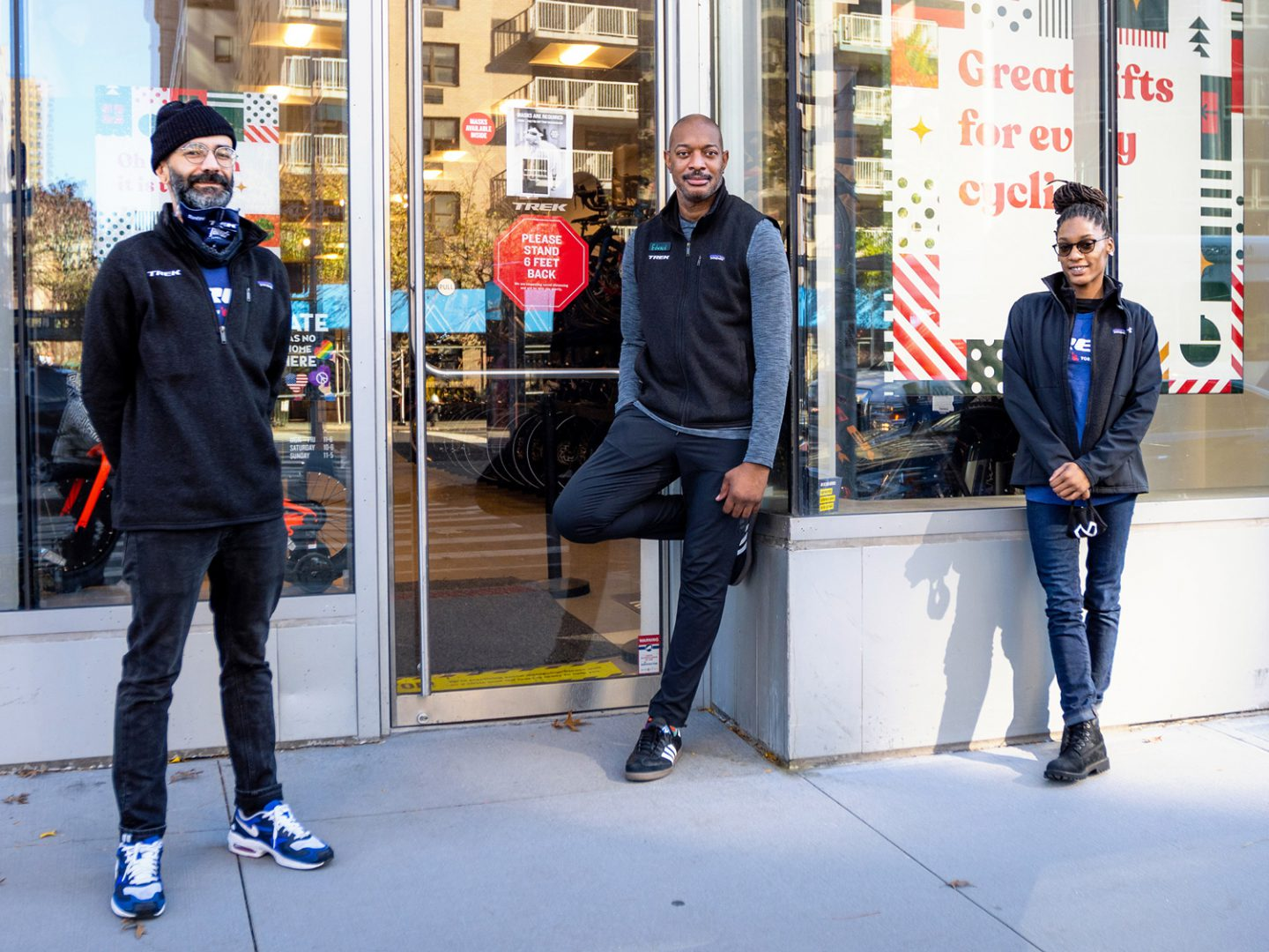 Three employees standing outside of a Trek store.