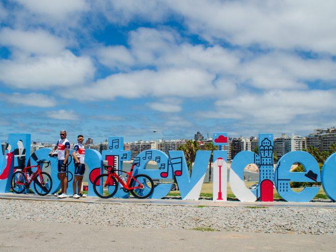 Dos ciclistas frente al cartel de la ciudad de Montevideo