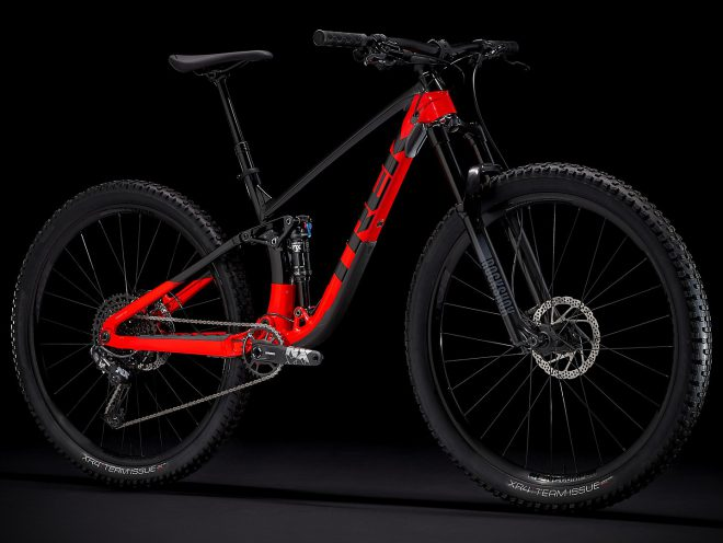 Black and red Trek Fuel EX 7 full suspension mountain bike on a black background