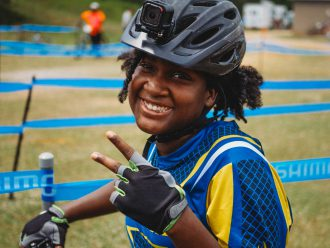 NICA student-athlete wearing a bike helmet, smiling and gesturing to the camera.