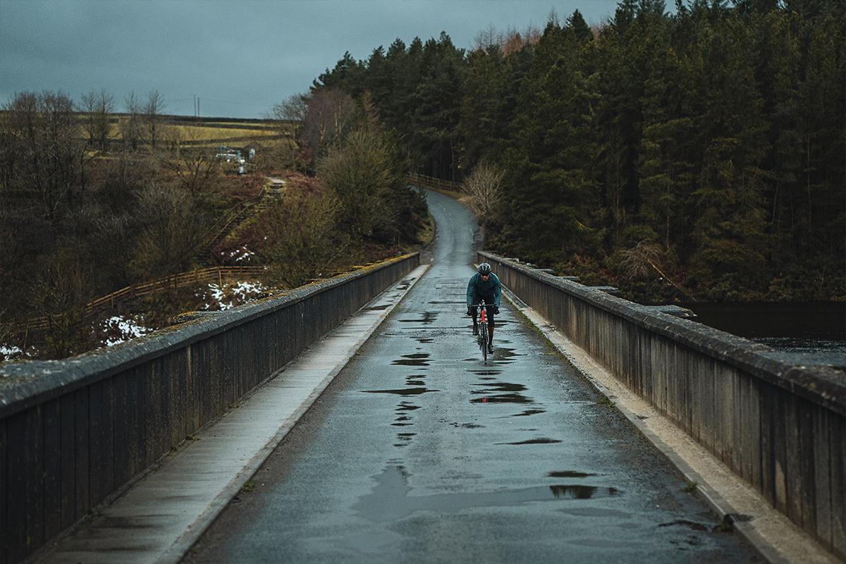 Märkä tie ja yksinäinen pyöräilijä alkavassa hämärässä