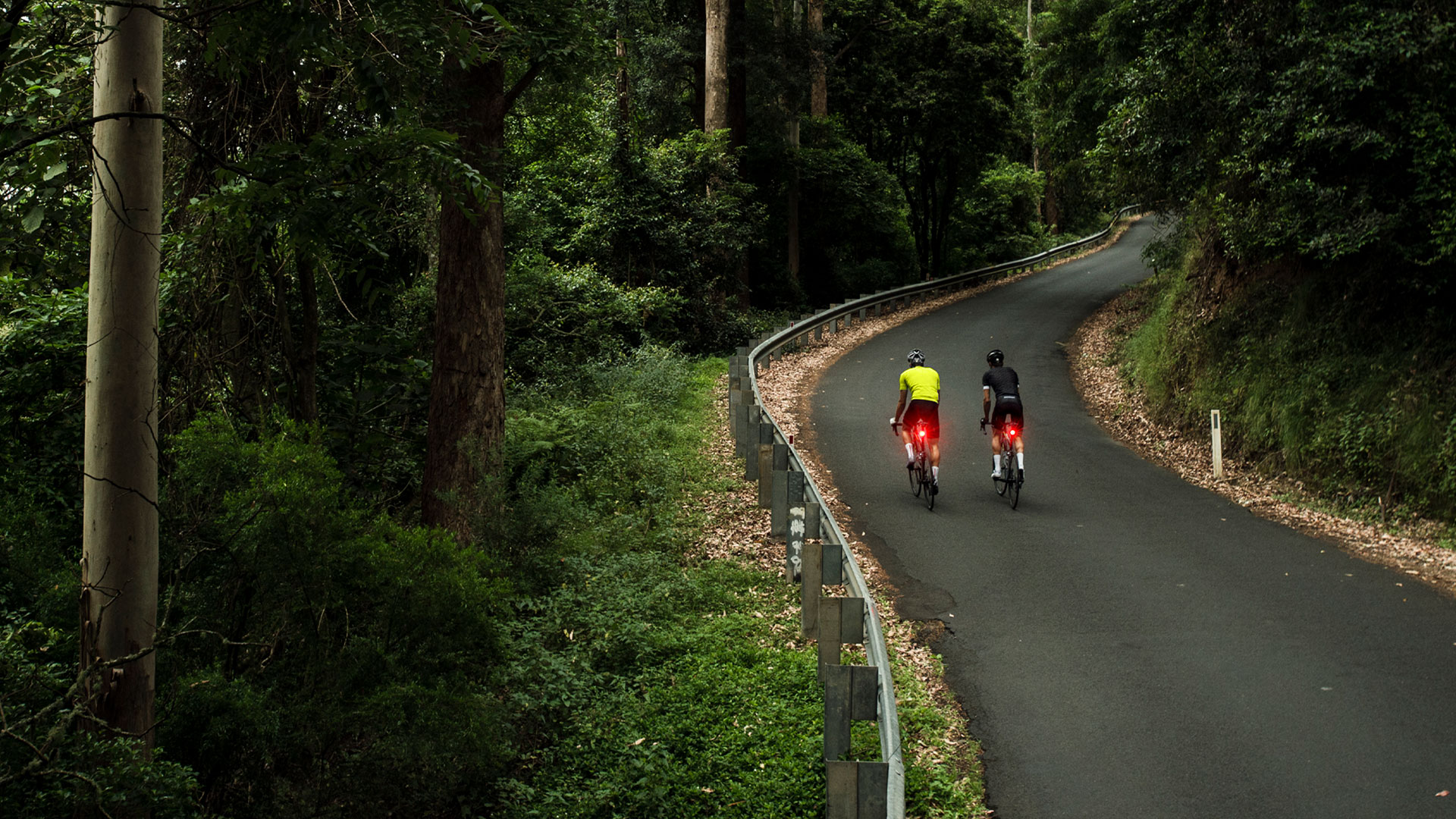 Two men riding with rear lights