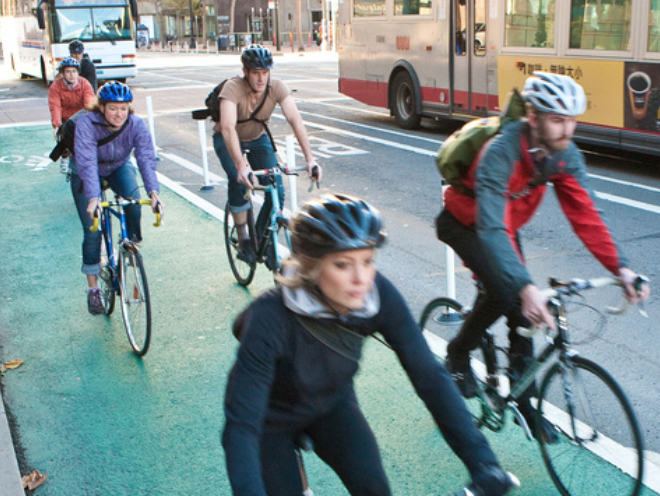 Cyclists ride in a city bike lane.