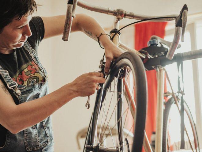 Mujer arreglando bicicleta