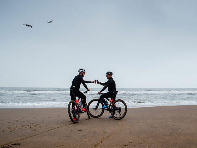 Maarten en Thijs proosten op het strand