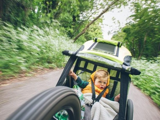 A child wearing a yellow vest rides behind a bicycle in a trailer on a dirt trail in a forest.