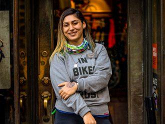 Woman (Tati Koufopanteli) standing in front of bike shop