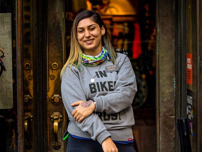 Žena (Tati Koufopanteli) stojící před cyklistickou prodejnou