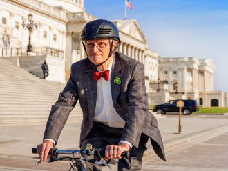Congressman Earl Blumenauer rides his bike in front of the US Capitol building. He is wearing a bicycle helmet and suit with a bright red bowtie.