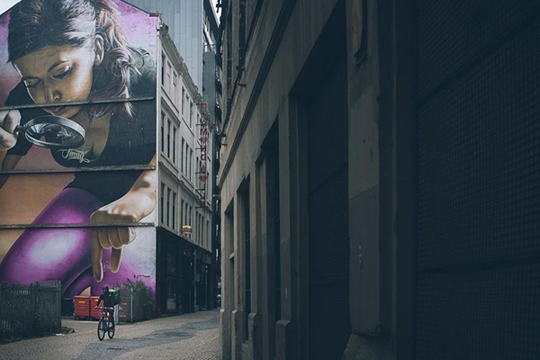 A photo of a cyclist riding down a dim back alleyway. Behind the cyclist is a large wall mural of a girl with a magnifying glass picking up something between her finger and thumb. The photo is taken so that it looks like the girl is about to pick up the cyclist in the foreground.