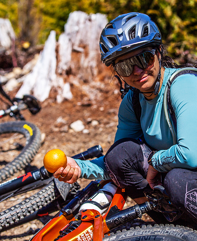Christina Chappetta crouching in front of her bike holding an orange