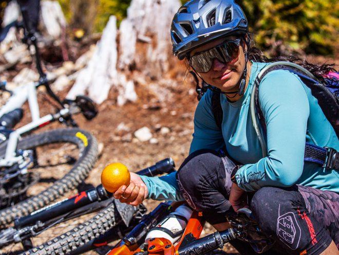 Christina Chappetta kniet vor ihrem Bike und hält eine Orange in der Hand