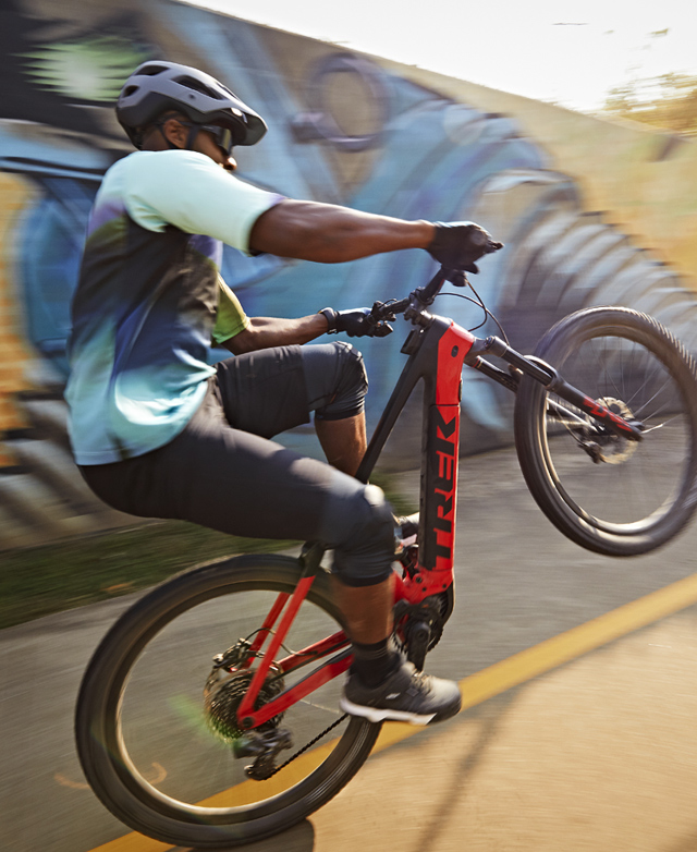A rider does a wheelie in a parking lot on his mountain bike with a graffiti wall behind him