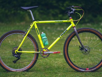 A fluorescent yellow Trek 6000 stands alone in a grassy field