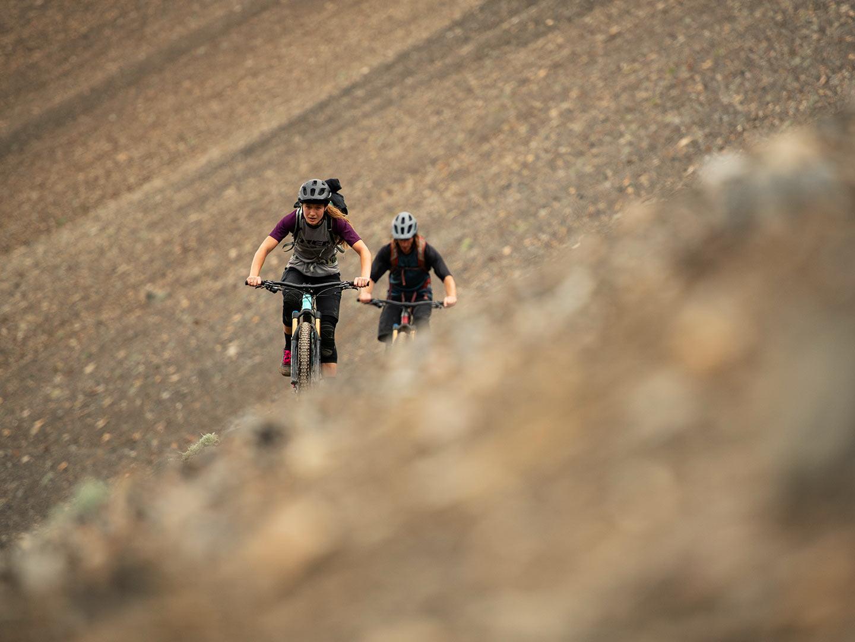 Riders climb up trail at high elevation above treeline