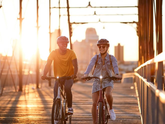 A man and a woman ride bikes across a bridge at sunset